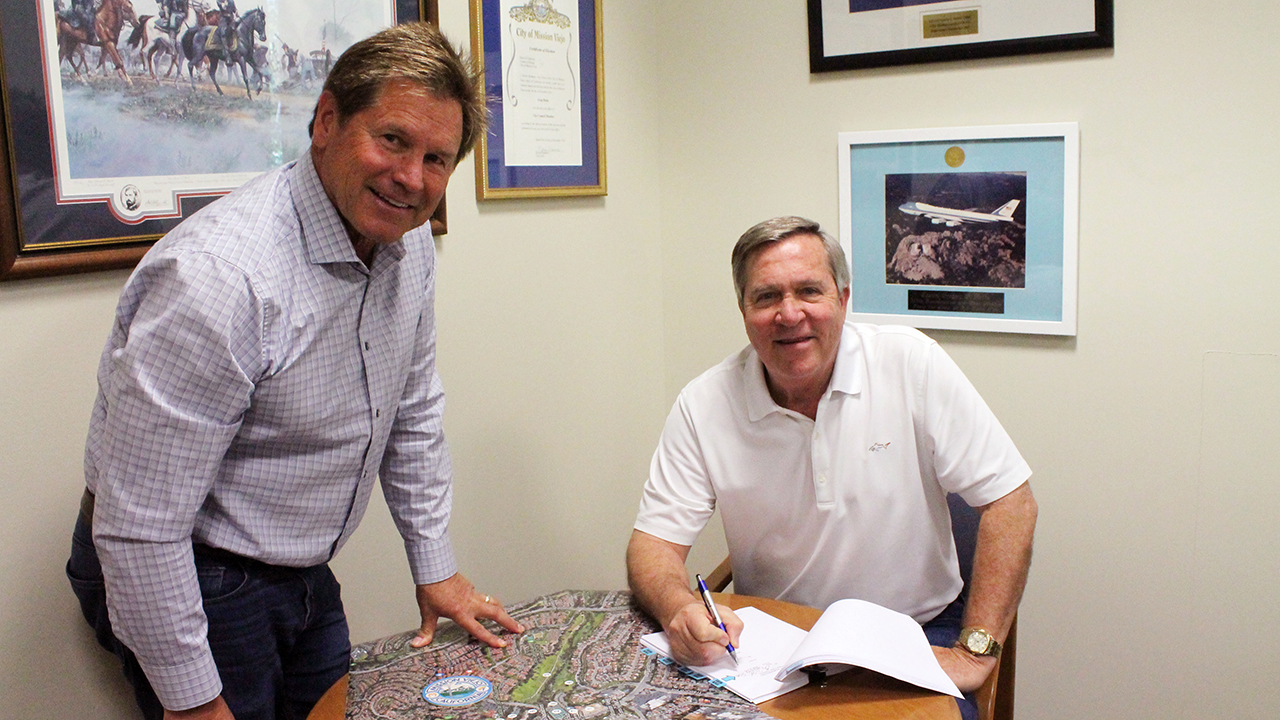mayor greg raths and brian goodell signing papers